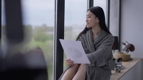 Happy Smiling Asian Female Freelancer in Bathrobe Looking Out the Window Sitting on Windowsill in
