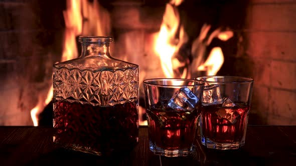 Thumbnail for Two Glasses and a Decanter of Whiskey Near the Fireplace