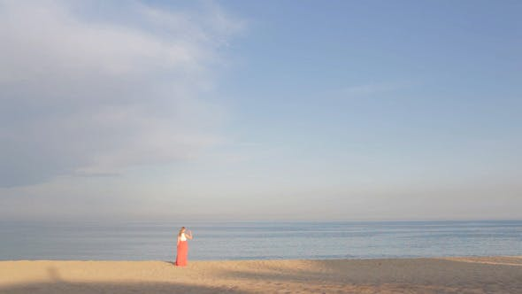 Thumbnail for Girl in Orange on the Beach