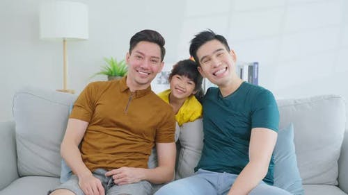 Portrait of handsome man gay family with young daughter sit on sofa in morning in living room.