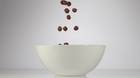 Chocolate balls falling in a white dish on a white background