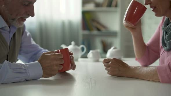 Cover Image for Male and Female Retirees Sitting at Table Talking Over Cup of Tea Happy Couple