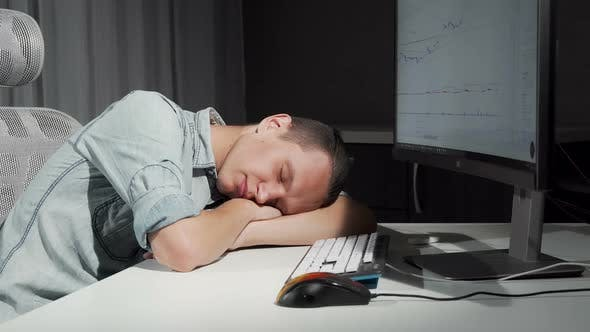 Thumbnail for Man Smiling in His Sleep Resting on the Desk in Front of the Computer