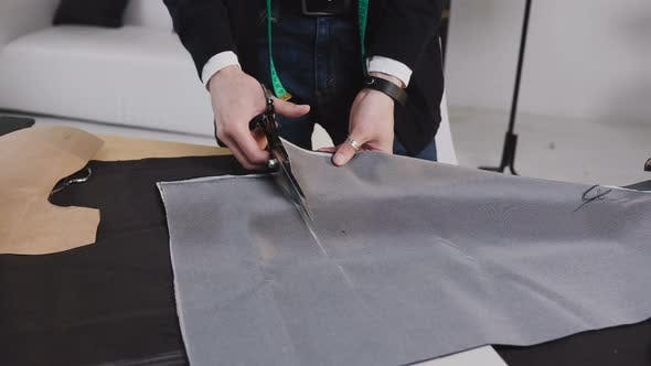 Thumbnail for A Tailor Cutting a High Quality Fabric Gray