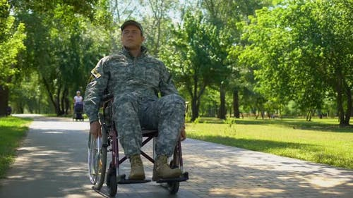 American Military Veteran Moving on Wheelchair in City Park, Health Care Program