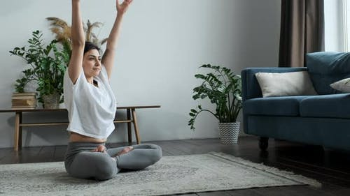 Asiatische Frau macht Yoga Übung Atmung und Meditation allein zu Hause. Bewegung und Training