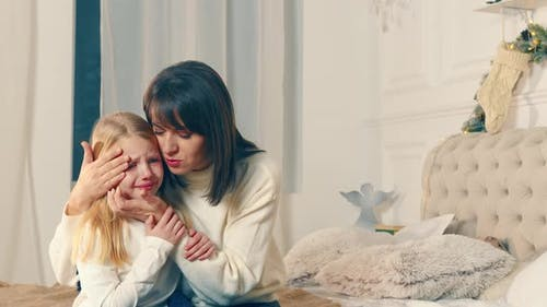 Mom Soothes a Crying Little Girl