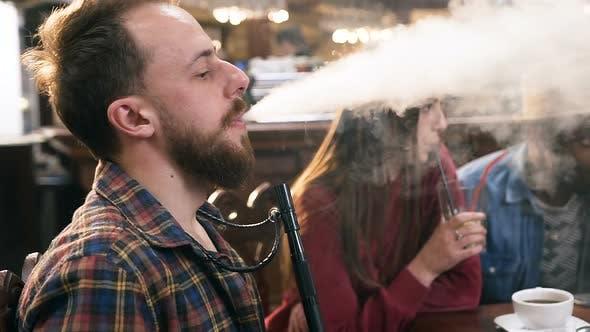 Thumbnail for Caucasian Young Man Smoking Hookah in the Bar