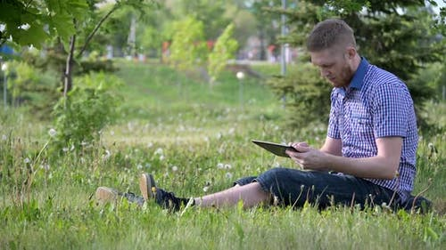 Young Caucasian Man is Swiping the Tablet Screen on the Green Lawn in City Park
