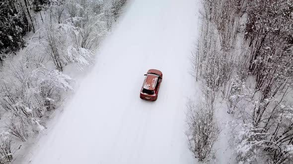 Cover Image for Aerial View of a Snowy Forest and Road with a Car in the Winter