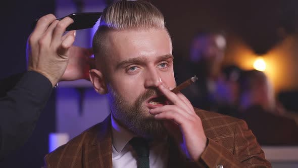 Hairstylist Does Hair Styling Hair To Businessman Smoking in Salon