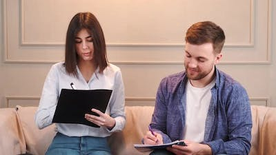 Married Couple Look at Papers at Couple Counsellor