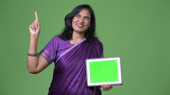 Thumbnail for Mature Happy Beautiful Indian Woman Thinking While Showing Digital Tablet and Pointing Finger Up