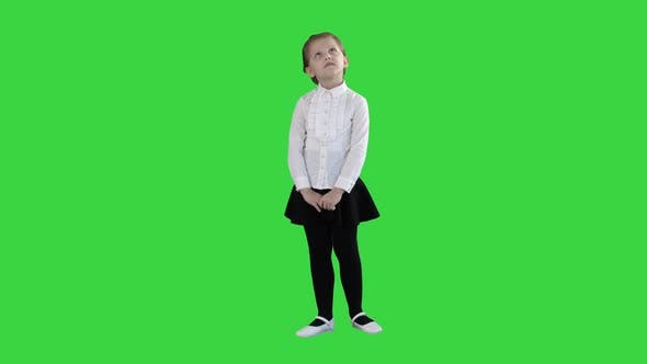 Thumbnail for Cute Preschool Girl Standing Being Shy Looking Around and Thinking on a Green Screen, Chroma Key