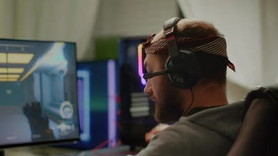 Focused Man Gamer Putting Headset Playing Shooter Online Video Game