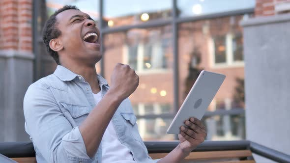 Thumbnail for Sitting Outdoor African Man Cheering Success on Tablet