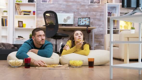 Thumbnail for Happy Caucasian Couple Eating Pizza Sitting on Pillow