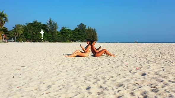 Thumbnail for Beautiful smiling ladies on photoshoot in the sun at the beach on clean white sand and blue 4K backg