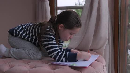 Ein kleines Mädchen Zeichnen mit Bleistiften zu Hause