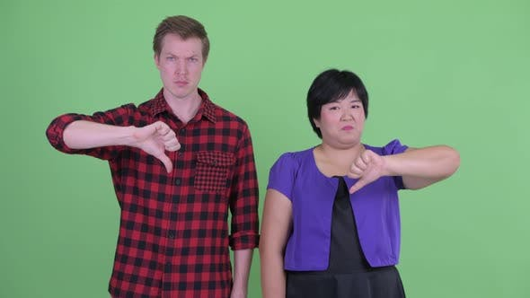 Thumbnail for Angry Young Multi Ethnic Couple Giving Thumbs Down Together