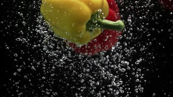Thumbnail for Yellow and Red Bell Peppers Splash Into Water on Black Background