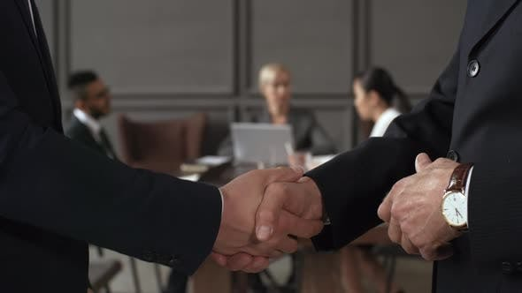 Thumbnail for Executives Shaking Hands during Corporate Meeting