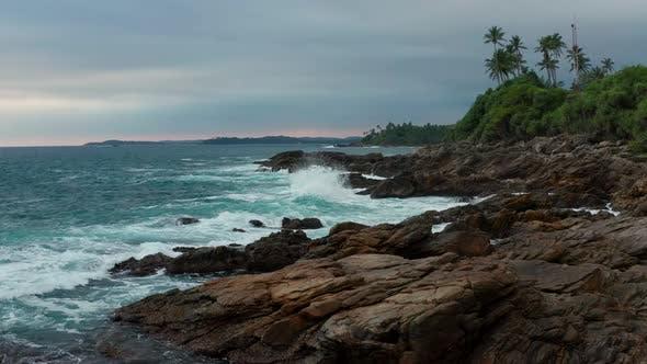 Ocean Waves Crash Against Stony Rocks During Sunset on the Island of Sri Lanka. Aerial View