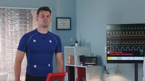 Middle Closeup of Athlete Walking on Treadmill and Female Doctor Coming to Monitor the Process