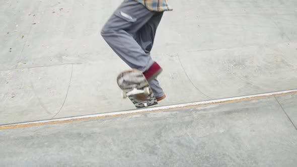 Skater Practicing in the Autumn Concrete Skate Park Making Tricks and Rides in Ramp