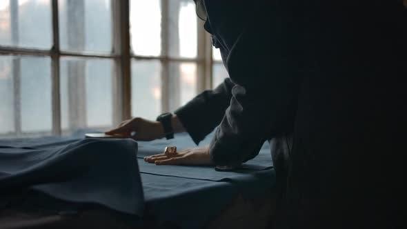 Die Hände der Frau, die das Wildledergewebe für die weitere Produktion glättet