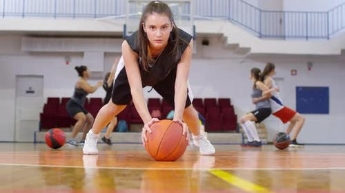 Junge weibliche Athlete tun Liegestütze mit Basketball