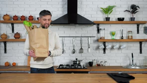 Smiling man comes to home kitchen puts paper bag with fresh vegetables on table