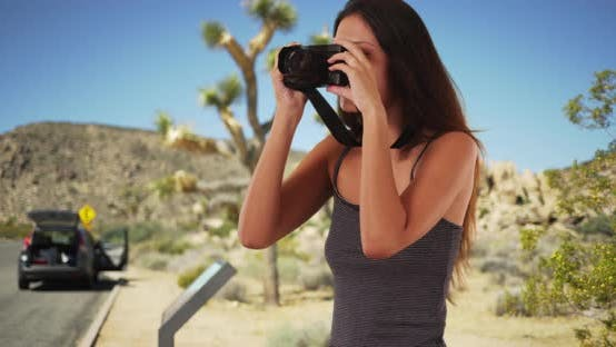Thumbnail for Pretty travel photographer in Joshua Tree taking picture with camera