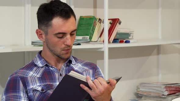 Thumbnail for Handsome Young Man Smiling Joyfully While Reading a Book