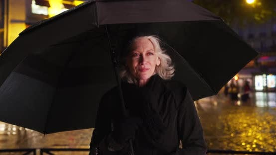 Thumbnail for Happy senior woman in Paris smiling under umbrella on rainy night in the city