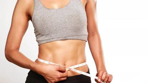 Slim perfect female body in sportswear measuring waist with measure tape