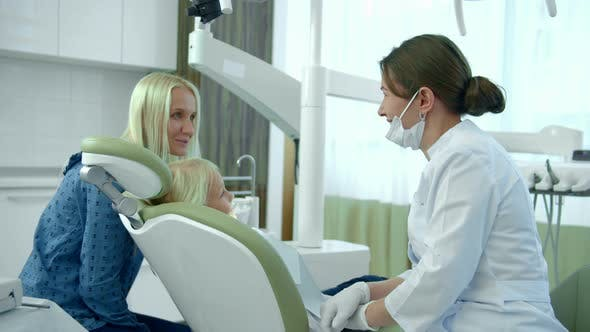 Cover Image for Little Girl Sits in a Dental Chair, Her Mother Talks To a Doctor