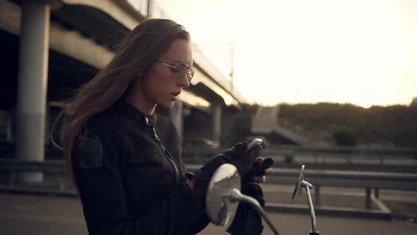 Side View of Moto Girl in Black Leather Jacket and Sunglasses Sitting on Motorbike Taking Off Gloves