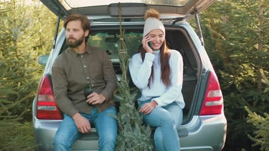 Thumbnail for Woman which Sitting Together with Her Husband in Car's trunk Among Beautiful Fir Trees