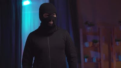 Thief in a Black Balaclava with a Flashlight in the House