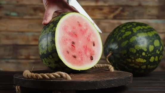 Male Hand with a Knife Cut Watermelon on a Wooden Tray.