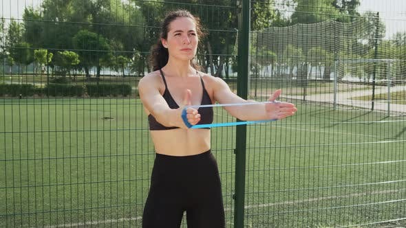 Young Woman in a Sporty Black Short Top and Gym Leggings Training with a Fitness Rubber Espander