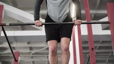 Athletic Concentrated Man Training on Bar in Gym