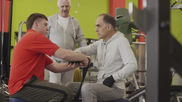 Thumbnail for Two Aged Sportsmen and Trainer in Gym