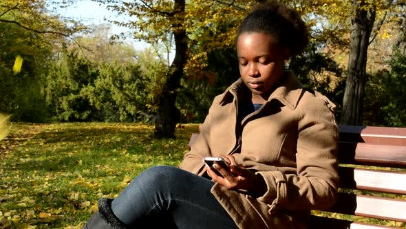 Thumbnail for Young Beautiful African Serious Girl Sits on Bench in Woods and Works on Phone