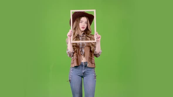 Thumbnail for Girl Is Holding a Wooden Frame and Posing As a Cowboy
