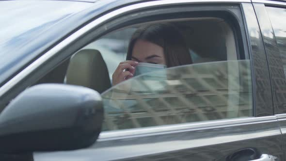 Thumbnail for Young Brunette Woman Putting on Protective Mask, Closing Side Window, and Getting Out of the Car