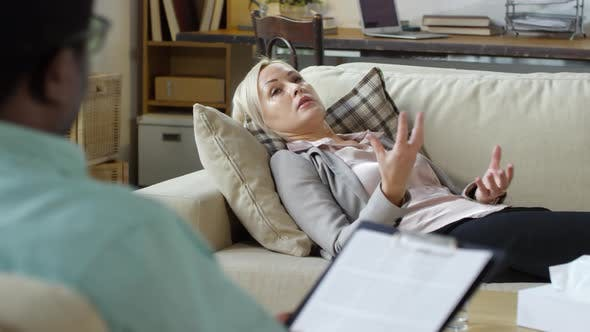Thumbnail for Middle Aged Woman Lying on Sofa and Talking to Male Psychotherapist