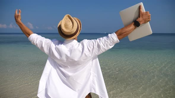 Thumbnail for Business Man With Arms Outstretched Holding Laptop Enjoying Beach Holidays