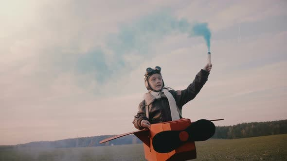 Thumbnail for Little Pilot Girl Running, Wearing Fun Cardboard Plane Costume with Blue Colour Smoke on Autumn